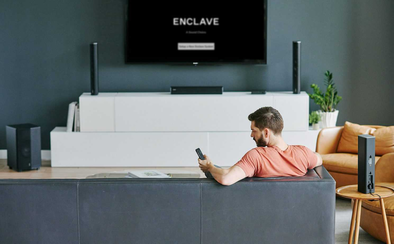 Enclave - CineHome Pro Man on Couch Setting Up