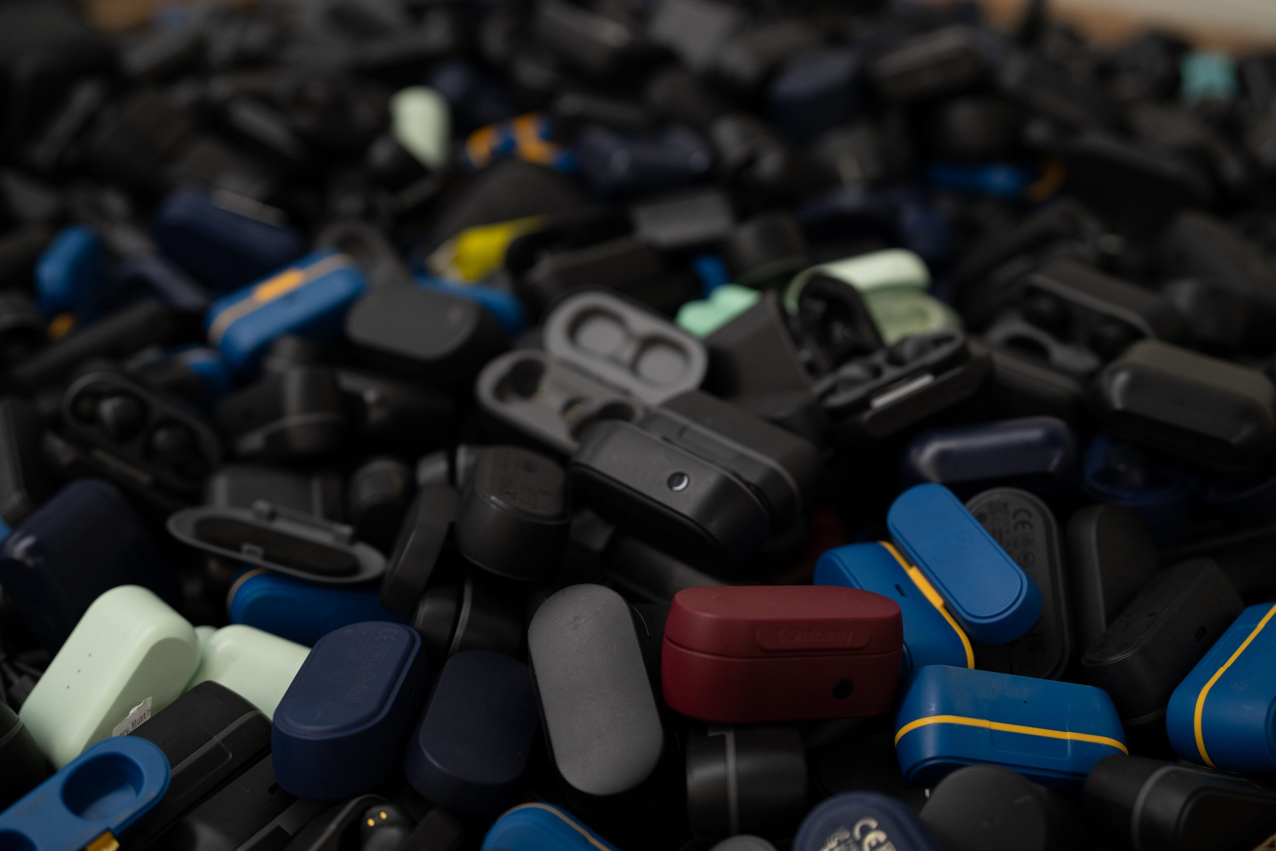 A pile of old Skullcandy wireless earbud charging cases