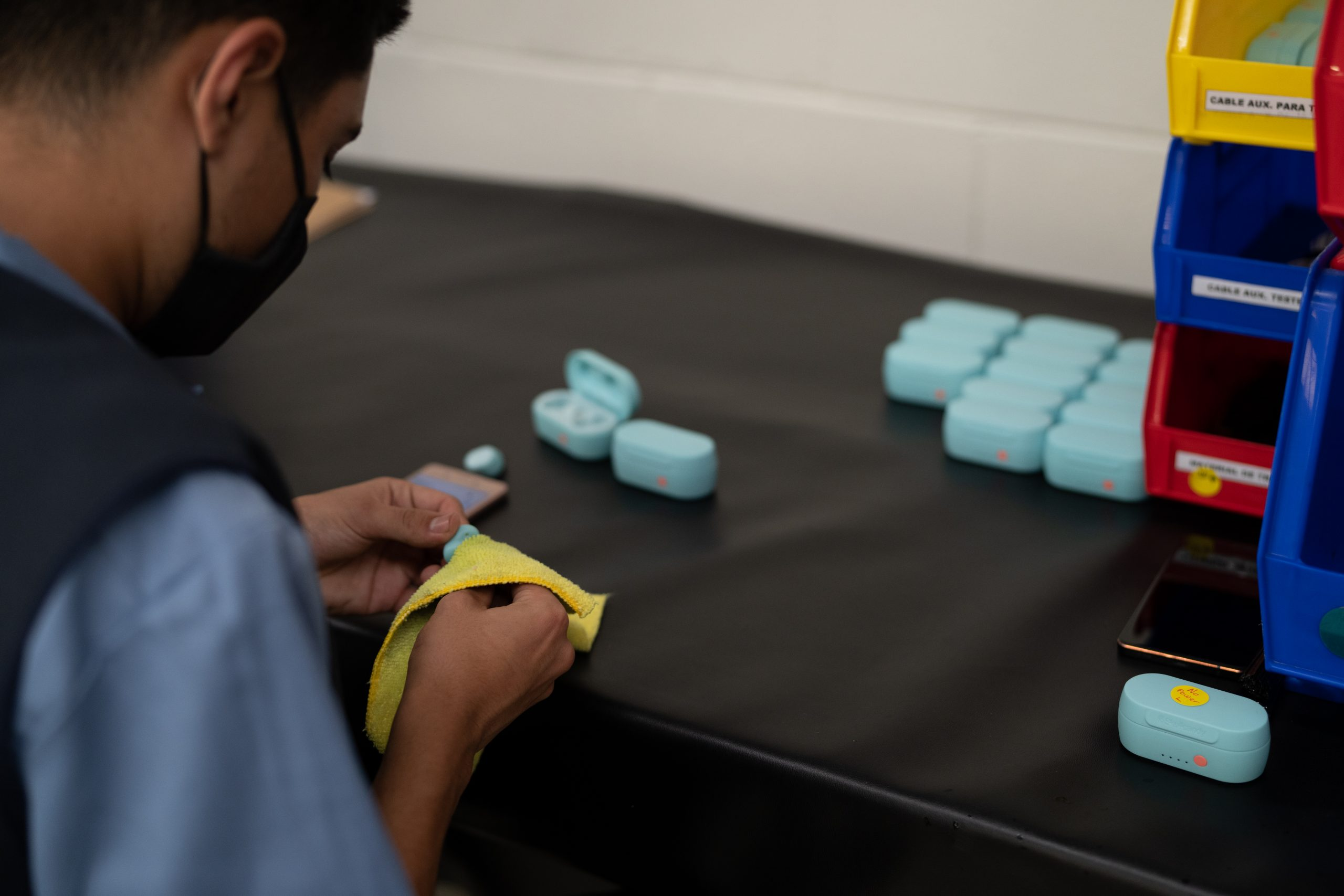 A worker cleaning upcycled Skullcandy earbuds with the charging case.