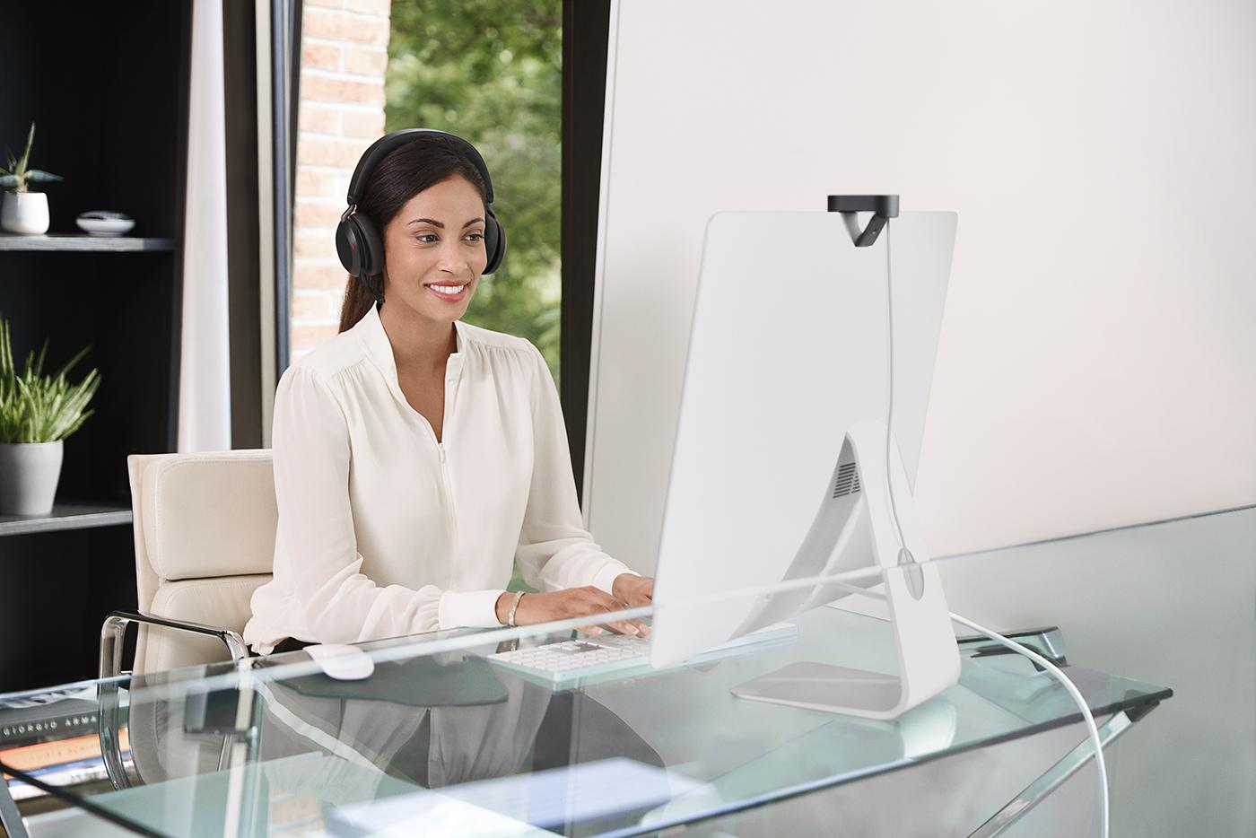 Remote work devices: A woman using Jabra headphones while on the computer.