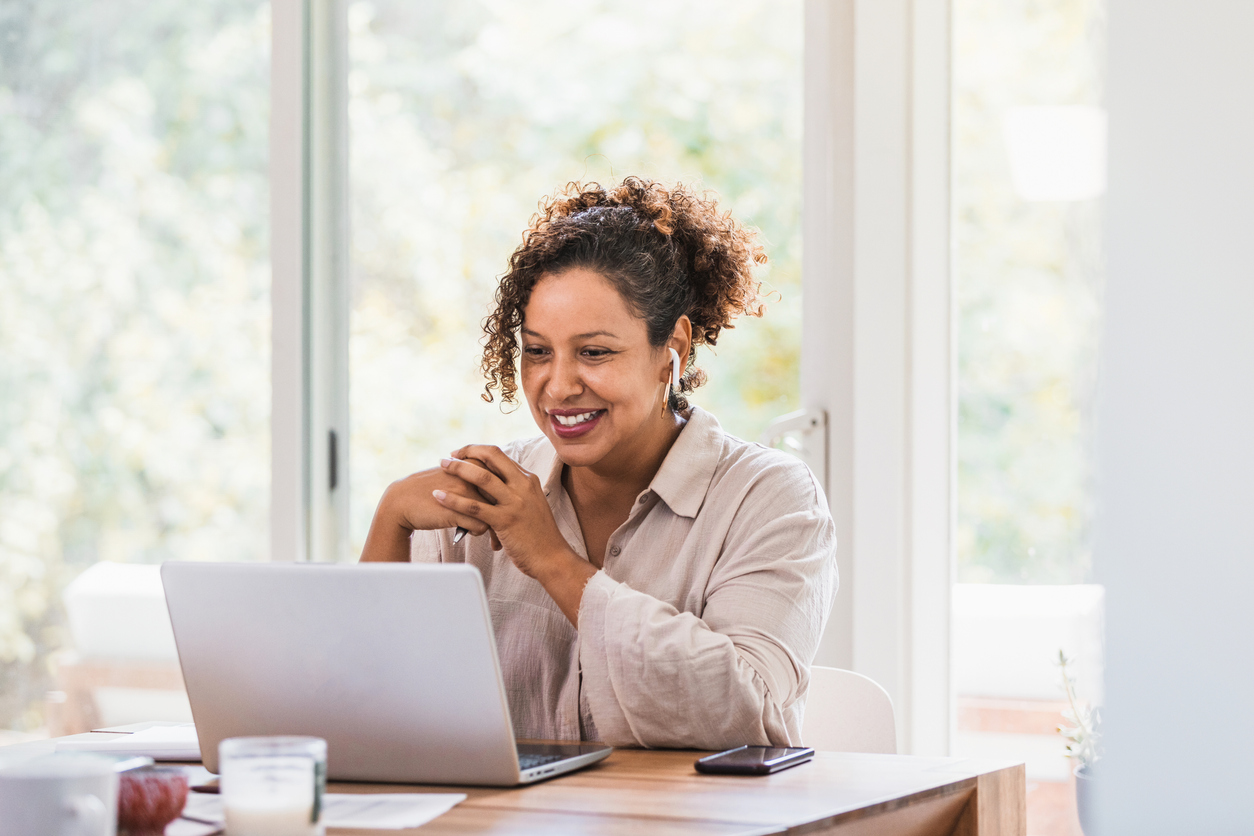 Remote work devices: A person with earphones talking on their computer.